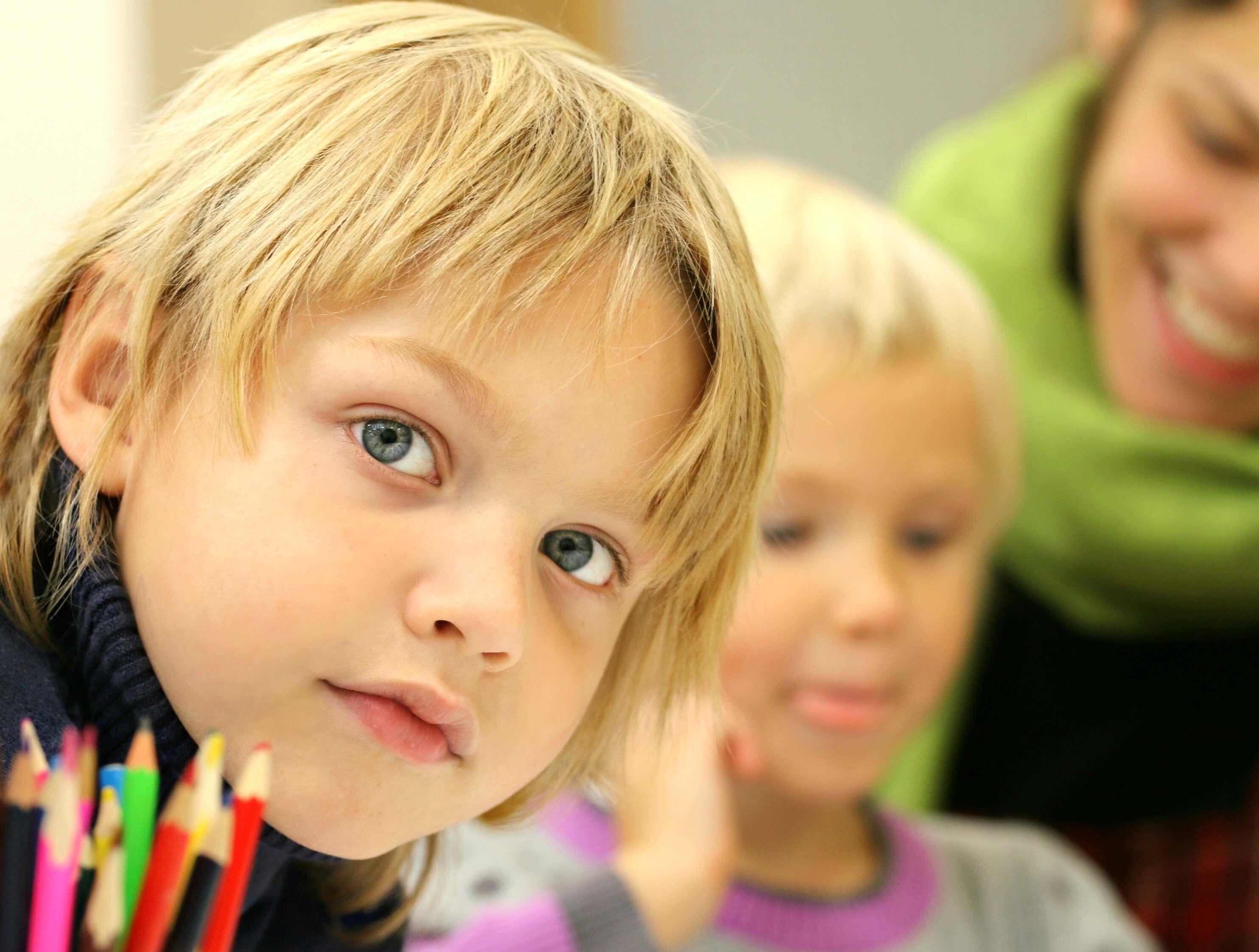 Ένα αγοράκι μας κοιτά ενώ κάθεται δίπλα από τις ξυλομπογιές του και τη συμμαθήτριά του στο σχολείο.